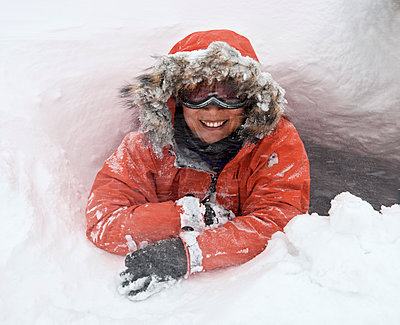 portrait of woman with faux fur hood and ski goggles in a snow hole - p1166m2268878 by Cavan Images