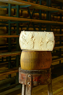 Cheese dairy master cutting a parmesan cheese wheel at the dairy - p1166m2290044 by Cavan Images