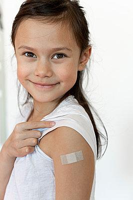 Kleines Mädchen mit Pflaster nach der Impfung, COVID-19 - p1625m2253785 von Dr. med.