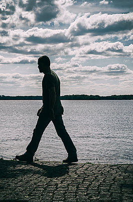 Man walking by the lake  - p794m1065474 by Mohamad Itani