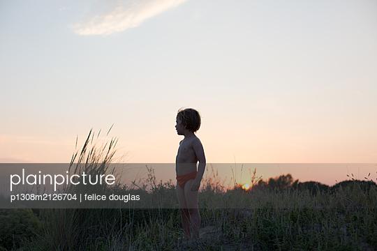 Boy in dunes by the beach - p1308m2126704 by felice douglas