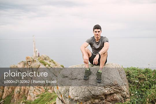 Portrait of trail runner sitting on a rock in coastal landscape, Ferrol, Spain - p300m2132362 by Ramon Espelt