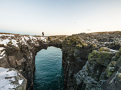 Mid distance view of hiker standing on natural arch over sea against sky - p1166m1543828 by Cavan Images