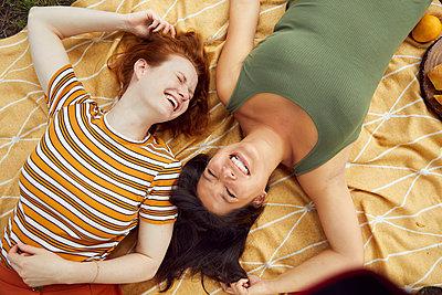 Two young women take a break on a picnic blanket - p1491m2176025 by Jessica Prautzsch
