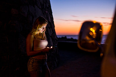 Woman using cell phone at sunset - p300m1537463 by Simona Pilolla