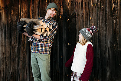 Happy father and daughter holding firewood in winter - p300m2160072 by Ekaterina Yakunina