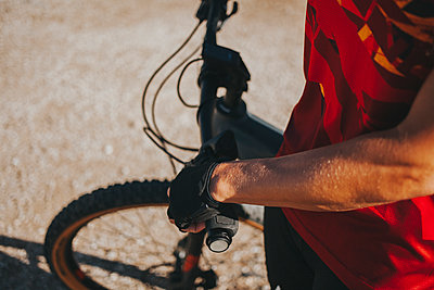 Hand of female cyclist holding bicycle handle on sunny day, Picos de Europa National Park, Cantabria, Spain - p300m2240206 by David Molina Grande