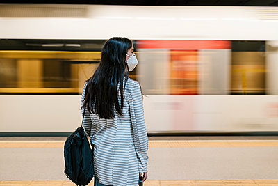 Woman waiting for her train at metro station during pandemic - p300m2240700 by Ezequiel Giménez