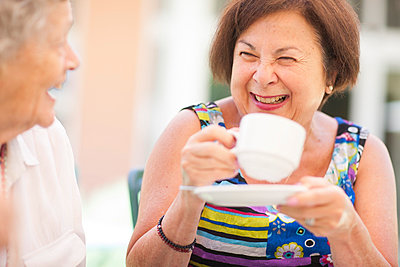 Two happy senior women drinking coffee together - p300m978830f by zerocreatives