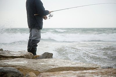 Fisherman fishing in stormy sea - p9248133f by Image Source