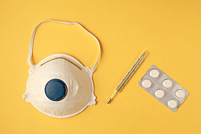 face mask or dust mask or respirator, pills and thermometer - corona virus covid19 - p1166m2174097 by Cavan Images