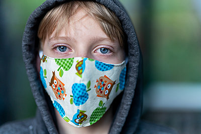 Close up of young person wearing face mask with hood on looking tired - p1166m2201954 by Cavan Images