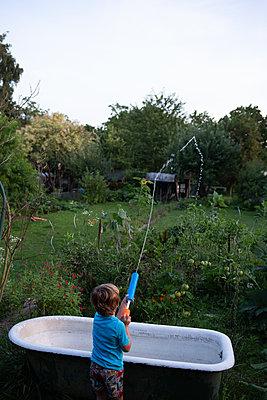 Kind mit Spritzpistole im Garten - p1308m2222829 von felice douglas