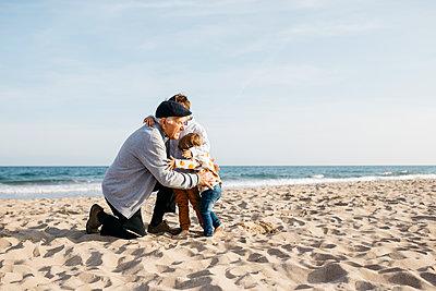 Grandfather hugging his grandchildren on the beach in spring - p300m2103159 von Josep Rovirosa