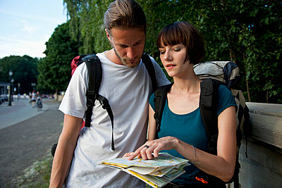A young backpacker couple looking at a city map - p30117713f by Marco Baass