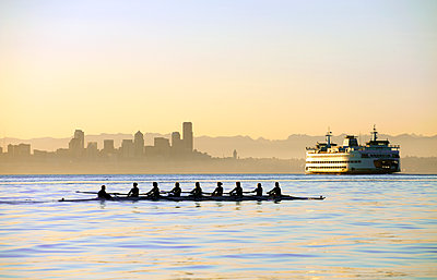 Team rowing boat in bay - p555m1478277 by Pete Saloutos