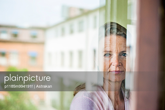 Mature teacher looking outside window with reflection of school building on glass
