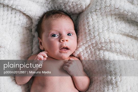 Portrait of baby girl lying on blanket - p300m2012887 von Mosuno Media