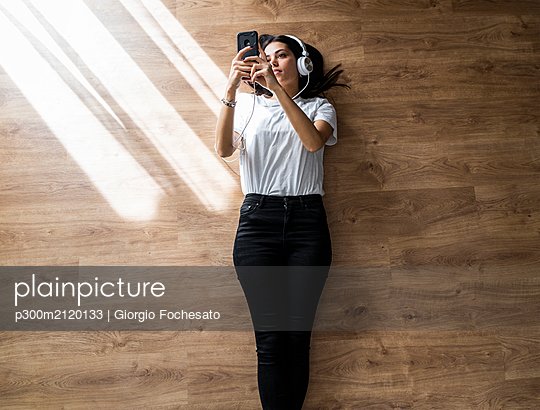 Young woman lying on the floor with smartphone and headphones - p300m2120133 by Giorgio Fochesato