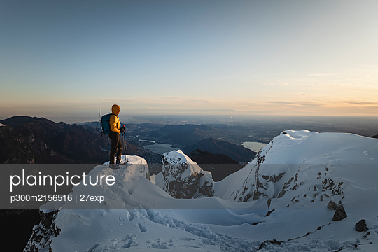 Mountaineer standing on top of a snowy mountain enjoying the view, Lecco, Italy - p300m2156516 by 27exp