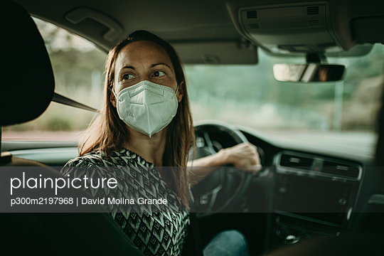 Mid adult woman with protective mask in car - p300m2197968 by David Molina Grande