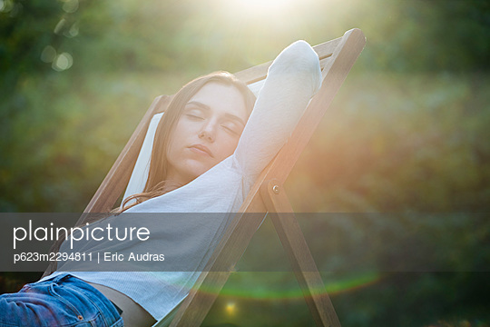 Young woman sleeping on chair in park - p623m2294811 by Eric Audras