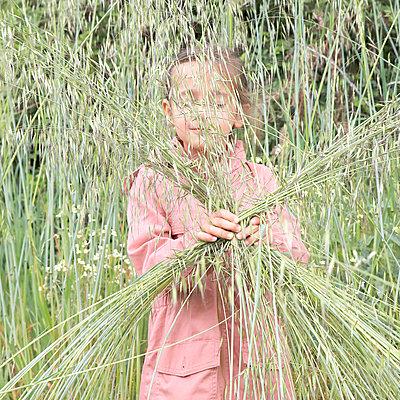 Little girl holding blades of grass in hand - p1105m2278331 by Virginie Plauchut
