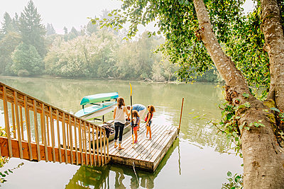 Family standing on dock in lake - p555m1306251 by Inti St Clair