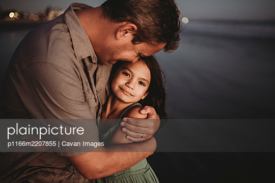Mid-40's dad hugging 8 yr old daughter on beach at sunset - p1166m2207855 by Cavan Images