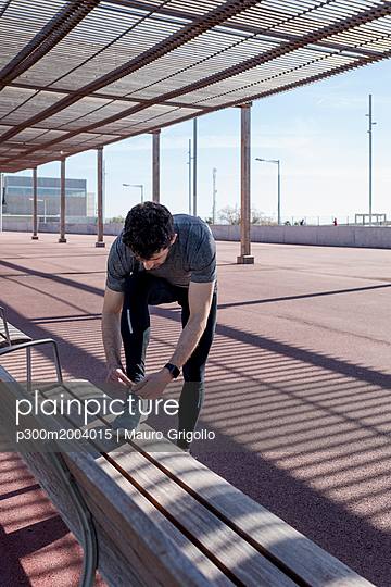 Sportive man lacing his shoes on a bench under roofing - p300m2004015 von Mauro Grigollo