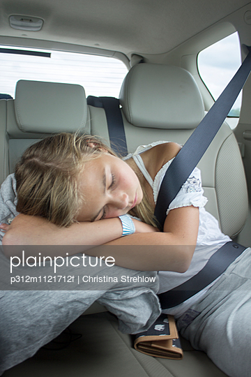 Girl sleeping in car - p312m1121712f by Christina Strehlow