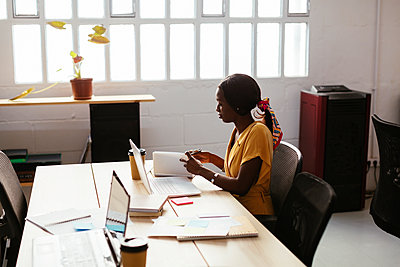 Young woman working at desk in office - p300m1587455 by Bonninstudio
