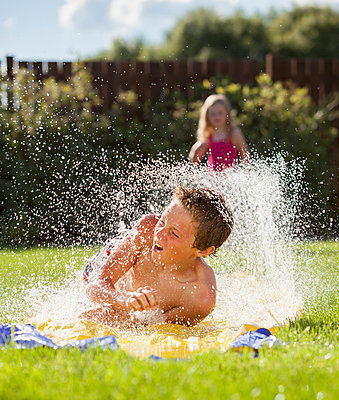 Caucasian boy sliding in water - p555m1479004 by Mike Kemp