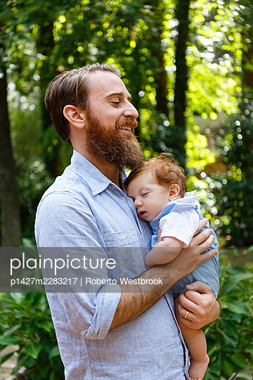 Father holding baby son, outdoors - p1427m2283217 by Roberto Westbrook