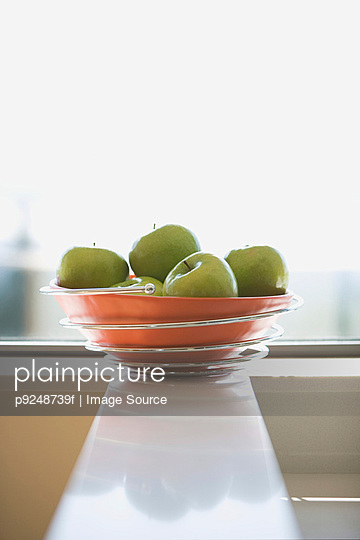Green apples in bowl - p9248739f by Image Source