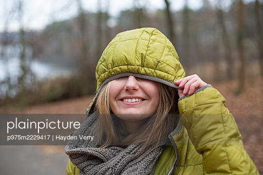 Junge Frau mit Schal und Kapuzenjacke - p975m2229417 von Hayden Verry