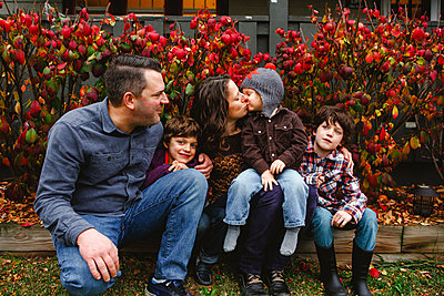 A mom kisses a little boy in her lap while their family fondly look on - p1166m2112926 by Cavan Images