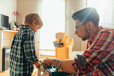 Father and son playing together on toy work bench - p300m1204554 by Zeljko Dangubic
