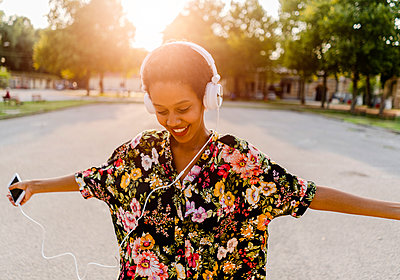 Happy fashionable young woman with headphones dancing outdoors at sunset - p300m2041984 by Giorgio Fochesato