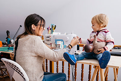 Happy mother with little daughter at home using sewing machine - p300m2058998 by Josep Rovirosa