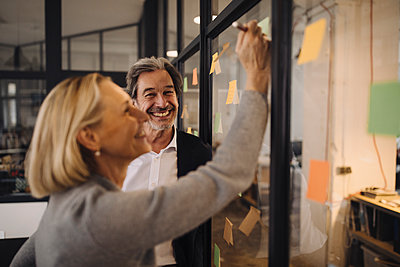 Happy colleagues with sticky notes at glass pane in office - p300m2143789 by Gustafsson