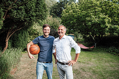 Smiling son with basketball standing with father in backyard - p300m2277001 by Gustafsson