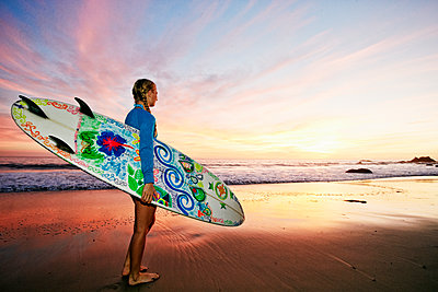 Caucasian woman carrying surfboard at beach - p555m1305263 by Peathegee Inc