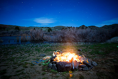 Burning campfire in remote field, Painted Hills, Oregon, United States - p555m1412144 by Adam Hester
