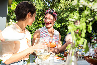 Friends have a chat on garden party - p788m1165311 by Lisa Krechting