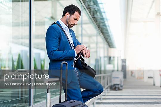 Businessman at airport, looking on watch - p300m1587062 von Daniel Ingold