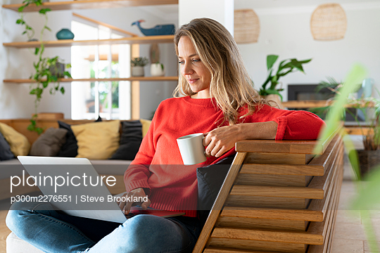 Blond woman using laptop while holding coffee cup in living room - p300m2276551 by Steve Brookland