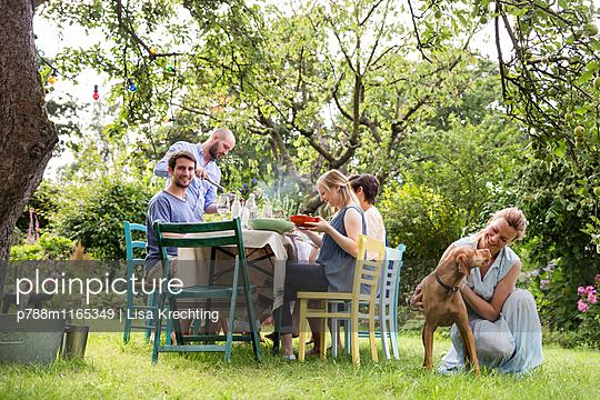 Frau streichelt Hund im Garten - p788m1165349 von Lisa Krechting