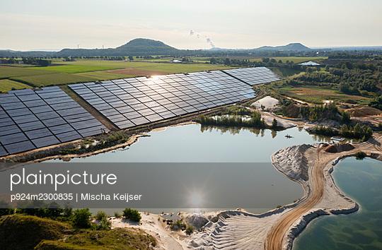 Germany, Herzogenrath, Aerial view of solar panels at sand mine - p924m2300835 by Mischa Keijser