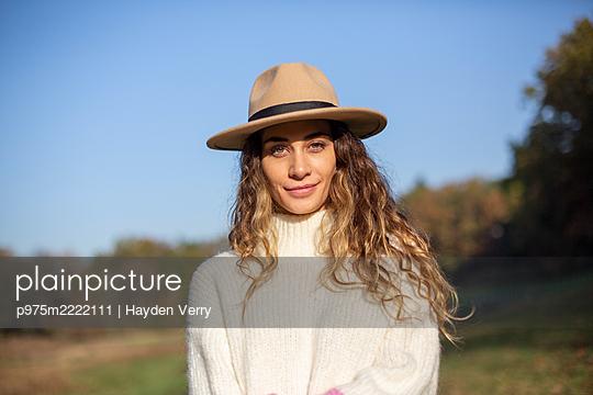 Junge Frau mit Hut auf einem Spaziergang - p975m2222111 von Hayden Verry